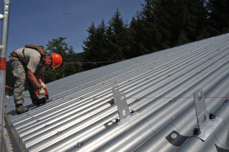 Metal Roof Cost In Minneapolis 2019 - Man Working on Metal Roof