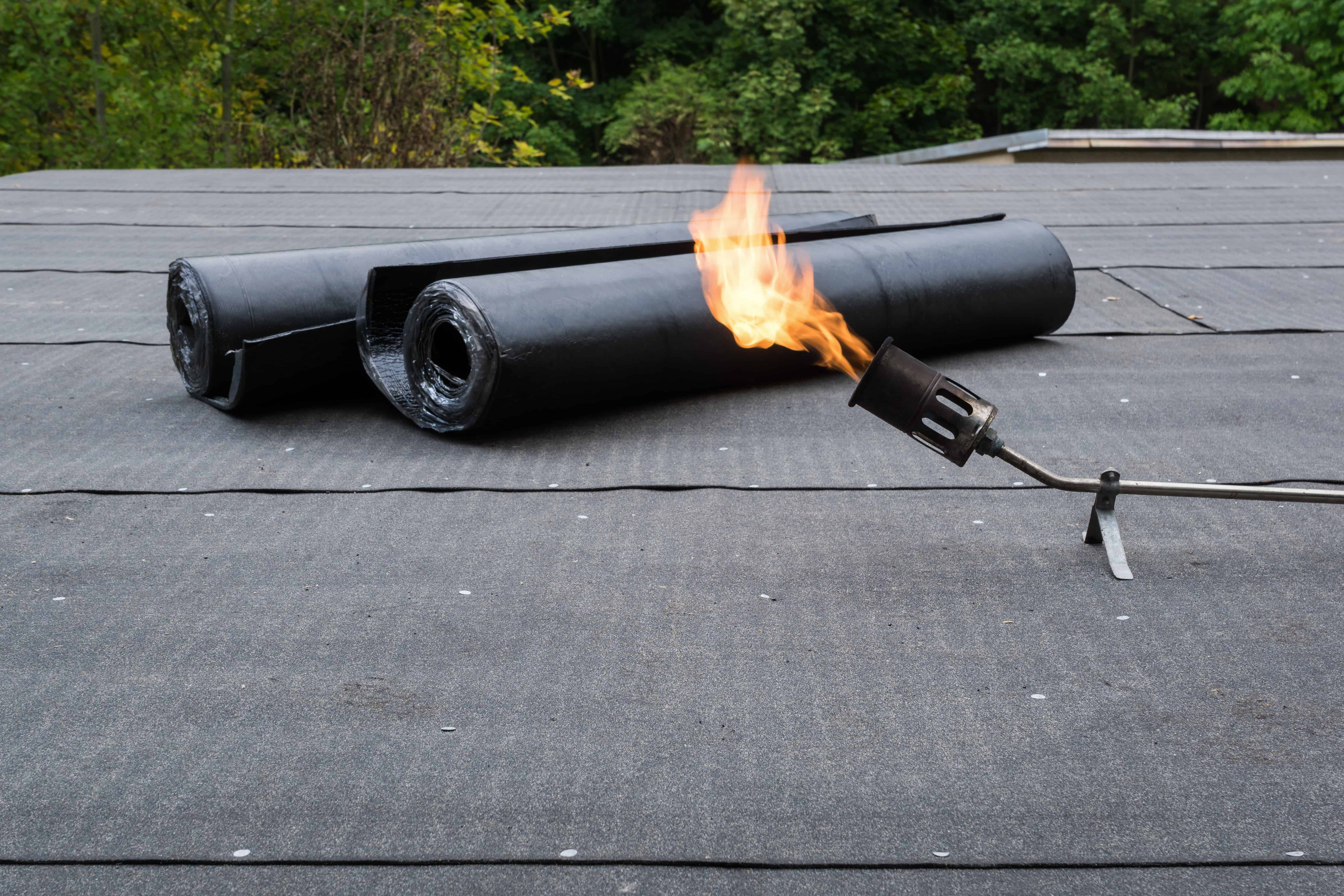 Flat Roof Materials - Torch On Roofing Materials next to a Lit Torch