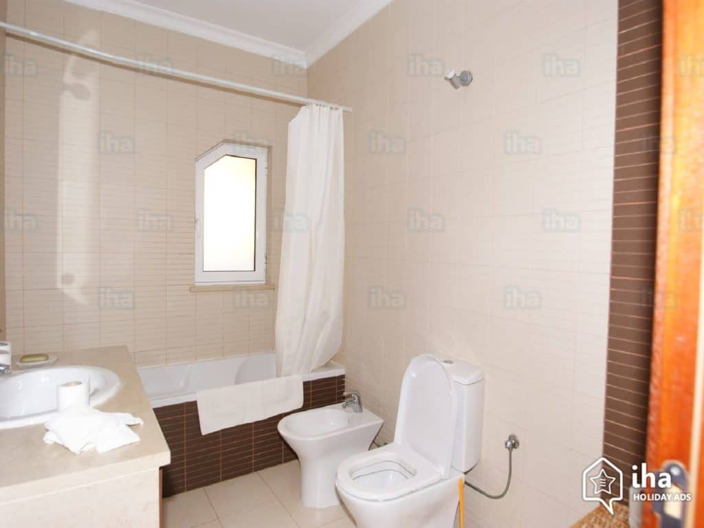 How to Start Remodeling a Bathroom - A Newly Remodeled Bathroom with FLowered Shower Curtain and New Flooring - Bathroom Lighting Picture Showing Light Entering a New Bathroom Remodel from a Small Window