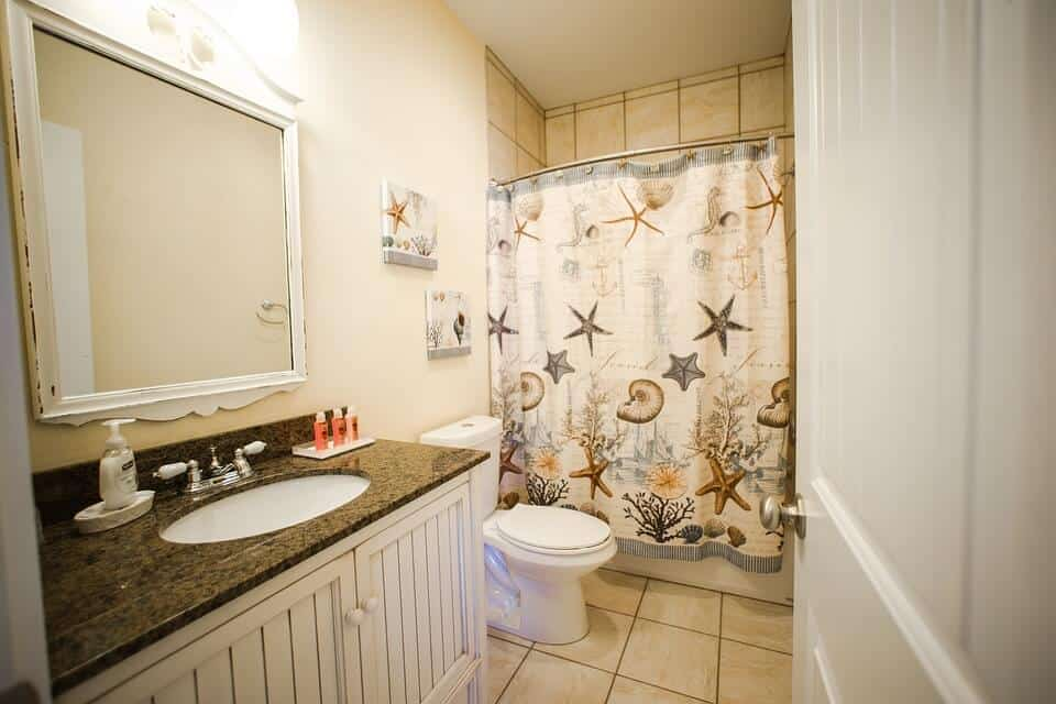How to Start Remodeling a Bathroom - A Newly Remodeled Bathroom with Flowered Shower Curtain and New Flooring