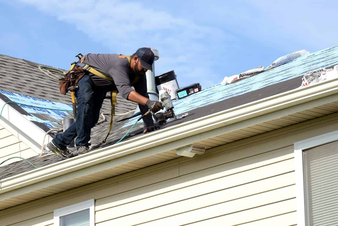 Are Roof Ridge Vents Necessary? - A Man Working on a Roof Installation with Tools Sitting on the Roof