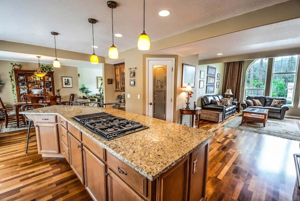 Worst Home Improvements for ROI - A Upscale Kitchen with an Island Stove and Brown and Tan Granite Countertops
