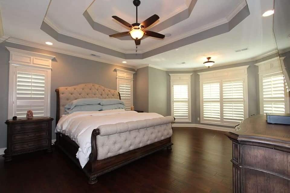 Worst Home Improvements for ROI - A Beautiful Master Bedroom Suite with Lots of Space, Wood Floors, and a Brown Wood Bed with Peach Colored Covers