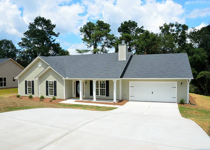 Is a Ridge Vent Better than Roof Vents? - A Yellow and White House with Garage