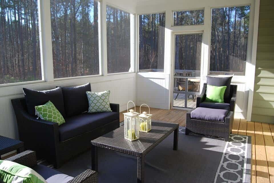 Worst Home Improvements for ROI - A Beautiful Sunroom Addition with Wood Floors and a Sofa and Pastel Gene and White Throw Pillows