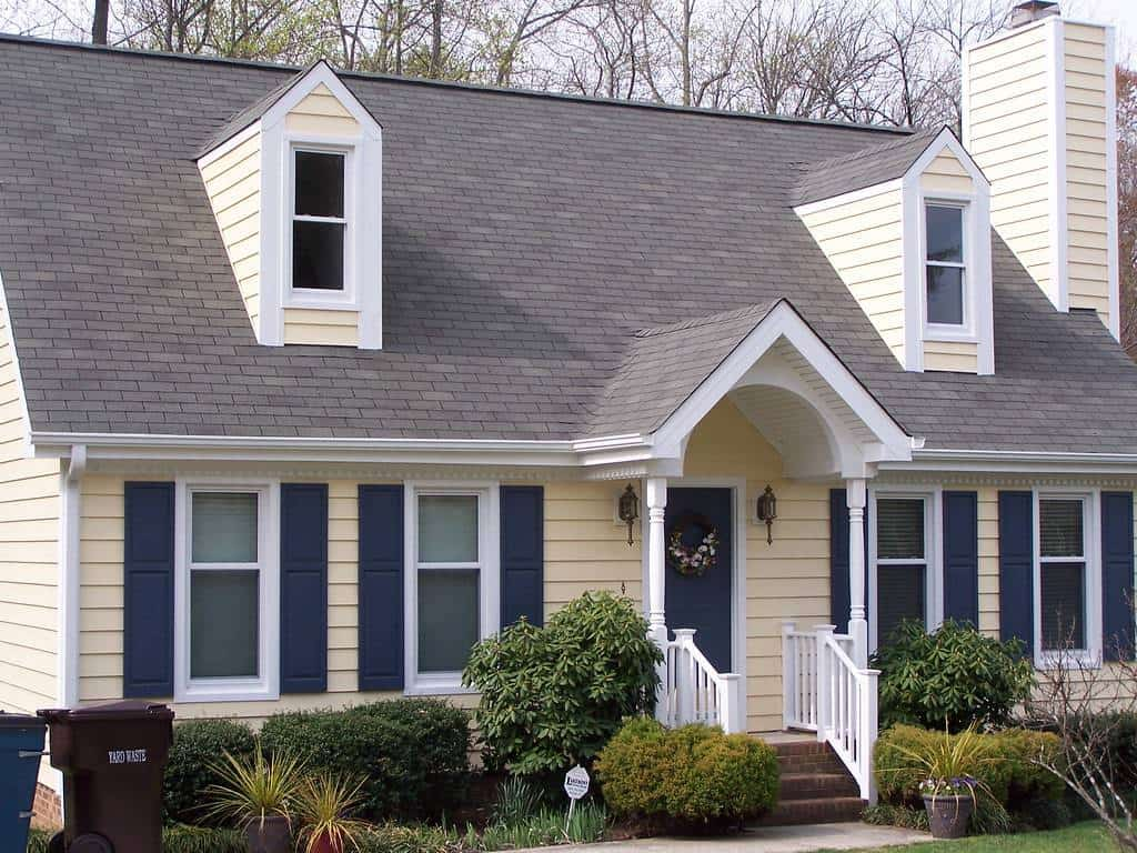 How Can You Tell if You Have Hail Damage On Siding? - A Home with yellow Siding and White Trim