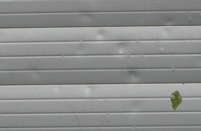 How Can You Tell if You Have Hail Damage On Siding? - A Garage Door with Large Dents from Hail Damage